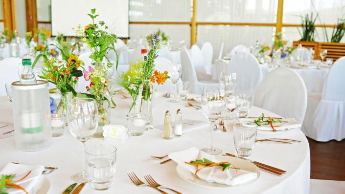 Hochzeits-Location Heckers Restaurant: Farbenfrohe Hochzeits-Dekoration mit Wiesenblumen im Veranstaltungsraum.